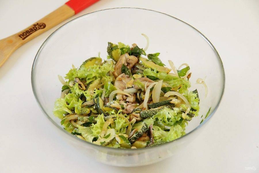 Добавьте листья салата и любую свежую сезонную зелень. Посолите, можно также добавить черный молотый перец и перемешайте. Салат из кабачков и шампиньонов готов.
