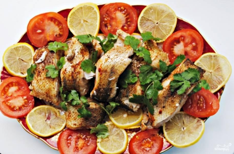 Когда судак сварится, аккуратно слейте воду из кастрюли, чтобы не повредить кусочки рыбы. Выложите их на блюдо и украсьте его овощами. Очень хорошо для украшения подходят кружочки томата и лимона, а также зелень.