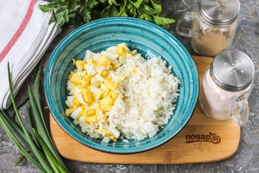 Очистите от скорлупы отварное куриное яйцо, промойте его в воде и нарежьте мелким кубиком. Выложите в глубокую емкость вместе с вареным рисом.
