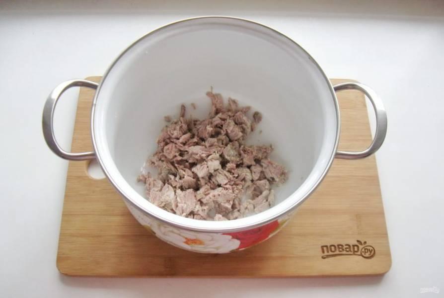 Отварное мясо нарежьте мелкими кубиками и выложите в кастрюлю.