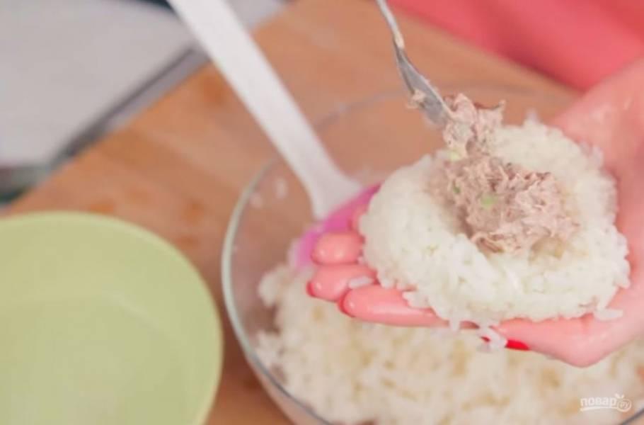 5. Далее сформируйте руками небольшие треугольники из риса, на середину выложите начинку и прикройте слоем риса. Заверните онигири в нори и посыпьте кунжутом. Приятного аппетита!