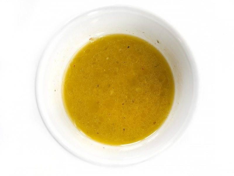 1.В миску выдавите 3 столовые ложки лимонного сока, нарежьте ломтиками оставшуюся половинку. Измельчите 2 зубчика чеснока, добавьте его к лимонному соку, а также влейте оливковое масло, соль и молотый перец, перемешайте.