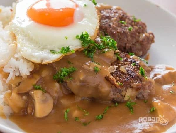 4.В отдельной сковороде разогрейте растительное масло и вбейте по одному куриные яйца, чтобы оставался жидкий желток. Отварите рис до готовности. Подавайте блюдо так: сперва выложите рис, затем котлеты, полейте подливкой, украсьте обжаренным яйцом и наслаждайтесь.
