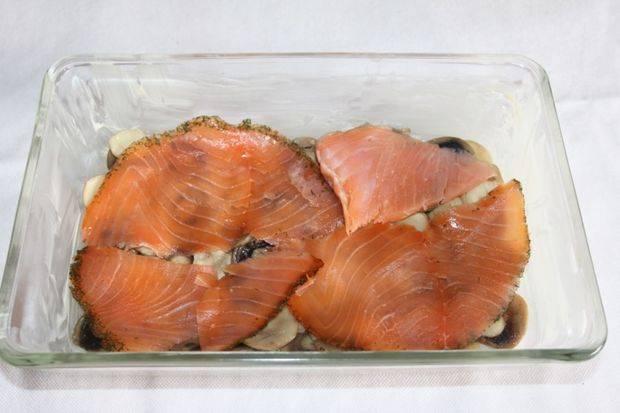 На грибы выложите тонкие слои лосося.