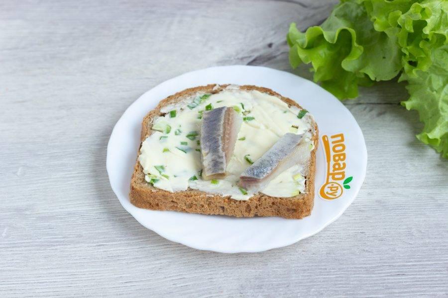 Хлеб намажьте луковым маслом, выложите на него филе сельди.