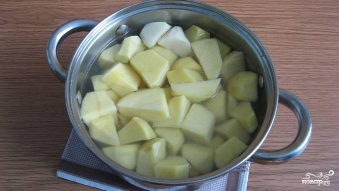 1. Картофель хорошо промойте под проточной водой, осушите и нарежьте небольшими кусочками. В кастрюлю налейте воды и выложите в неё картофель. Варите картофель до мягкости на среднем огне примерно 25 минут после закипания воды, после чего воду необходимо слить.