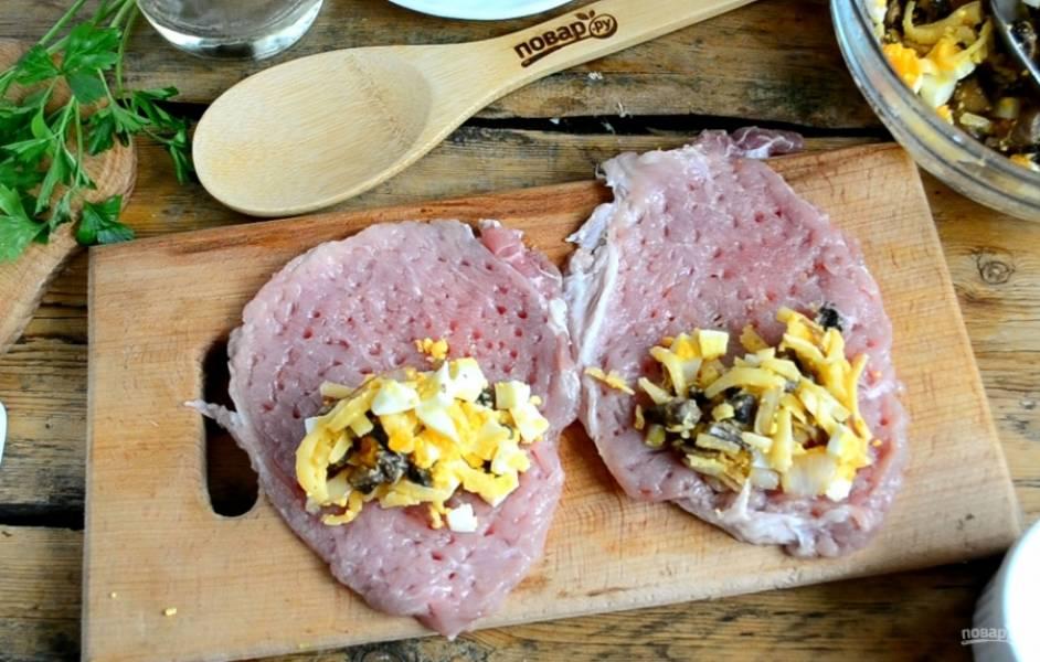 Свиную вырезку порежьте на пластины толщиной около 5-6 мм. Отбейте каждую пластину, посолите и поперчите с обеих сторон. На каждый кусок мяса положите примерно 1 ст. ложку начинки. Заверните мясо в рулетики.