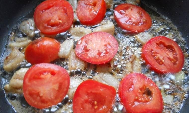 Обжариваем на сковородке до прозрачности и затем добавляем мелко нарезанный лук, обжариваем перемешивая, до золотистости. Сверху выкладываем помидоры, нарезанные кружочками.
