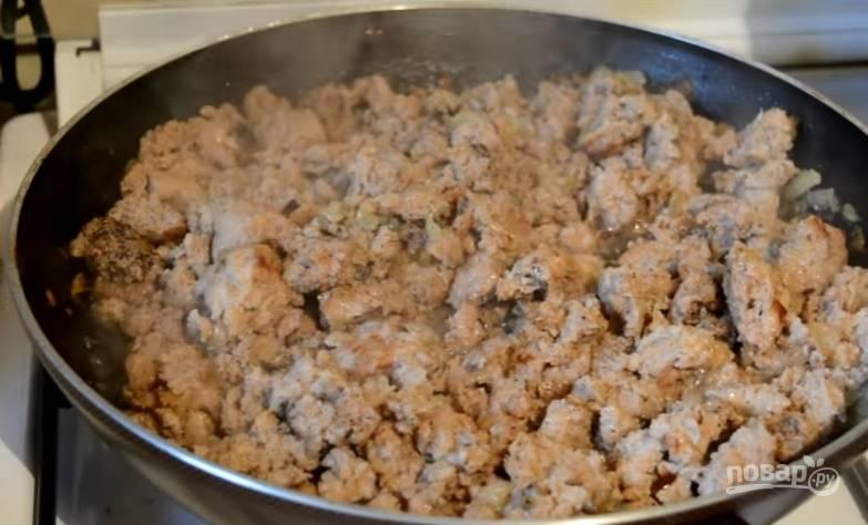 2. Лук очищаем и моем, после этого нарезаем кубиками и обжариваем на сковороде с растительным маслом. После этого выкладываем к нему фарш, разминаем лопаткой, солим и перчим.