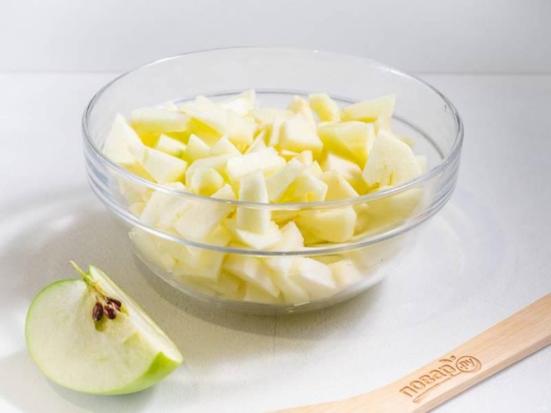 Яблоки очистите от сердцевины и кожуры, нарежьте на небольшие кусочки. Половинку одного яблока оставьте, чтобы выложить сверху шарлотки.
