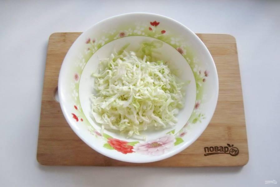 Капусту нарежьте тонкой соломкой и немного пожмите руками. Выложите в салатник.