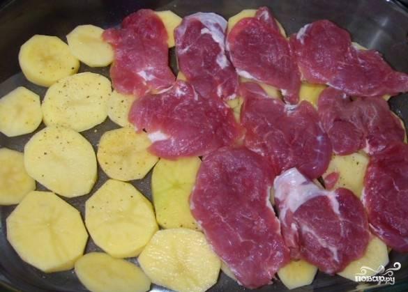 Картофель чистим и нарезаем пластинками, выкладываем его на противень, солим и посыпаем перцем. На картофель выкладываем кусочки свинины, так же посыпаем солью и специями.