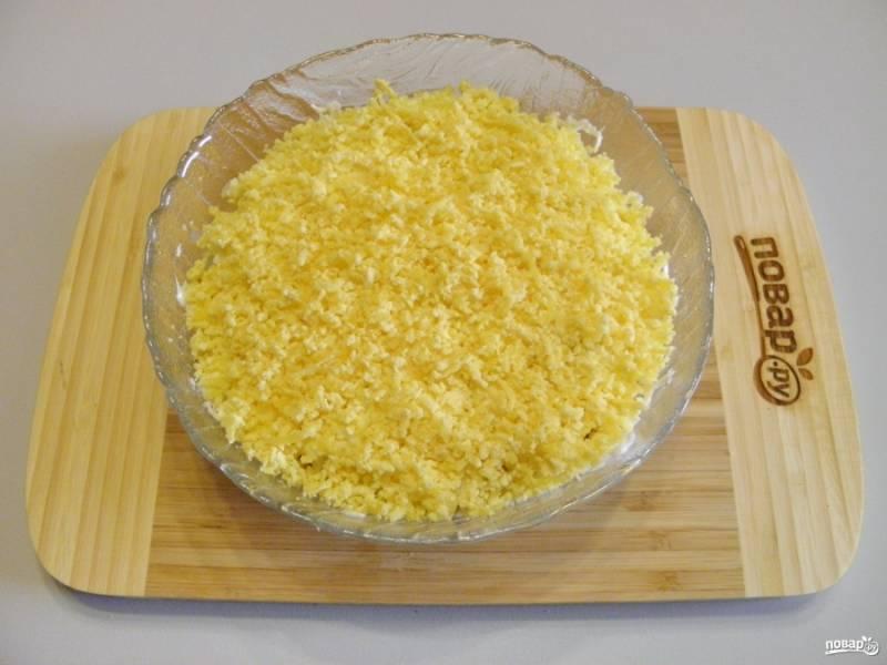 Последний слой - тертые на мелкой терке яичные желтки. Теперь накройте салат пищевой пленкой и поместите его в холодильник на 1,5-2 часа.