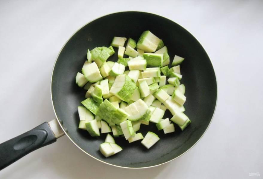 Два кабачка среднего размера помойте и нарежьте кубиками. Молодые кабачки чистить не обязательно. Выложите кабачки в глубокую сковороду.