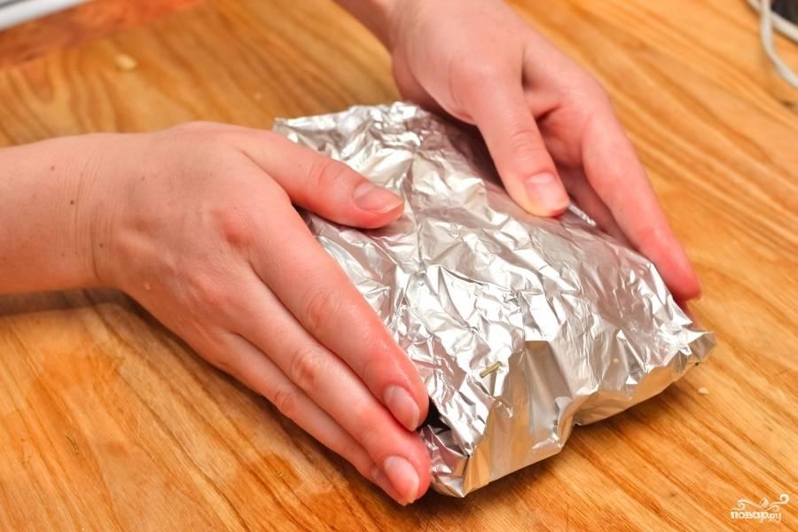 Аккуратно заверните стейк из лосося в фольгу.