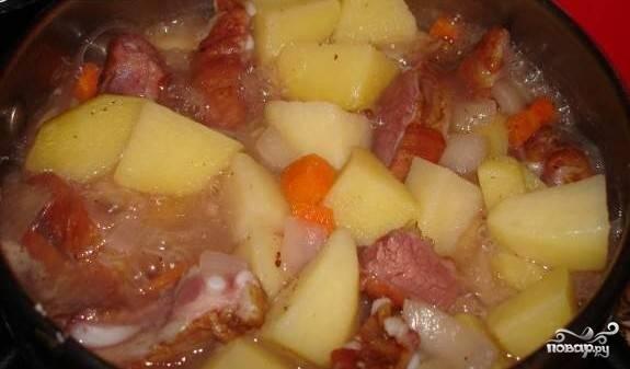 7.Спустя 10 минут после того, как добавили в кастрюлю картофель, всыпаем туда нарезанные морковь и лук. Солим, перчим. Можно также добавить приправы на собственное усмотрение. Хорошо подойдет раздавленный чеснок (1 зубчик). Перемешиваем содержимое кастрюли. Варим до готовности картофеля.