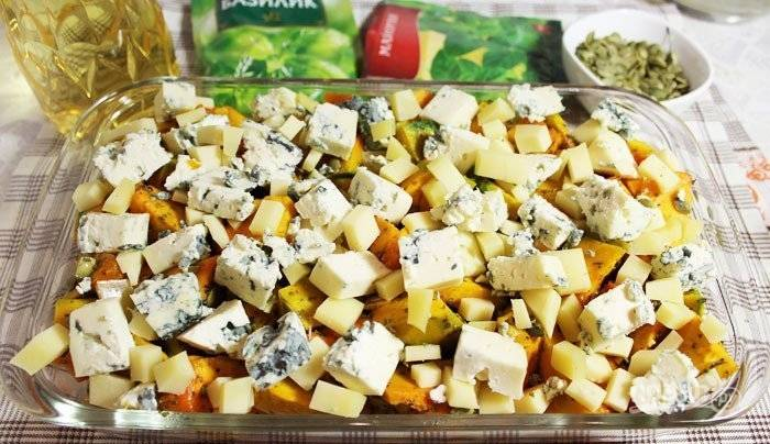 На курицу выложите тыкву, а сверху выложите оба вида сыра (кубиками).
