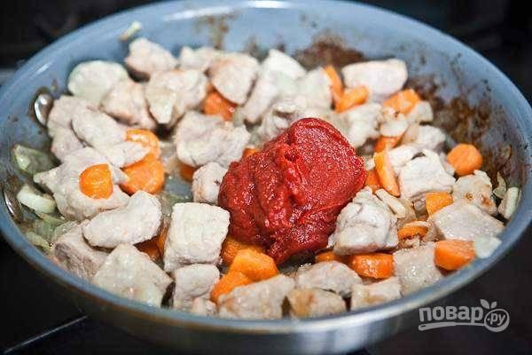 7. Выложите на сковороду томатную пасту, аккуратно перемешайте и тушите еще несколько минут.