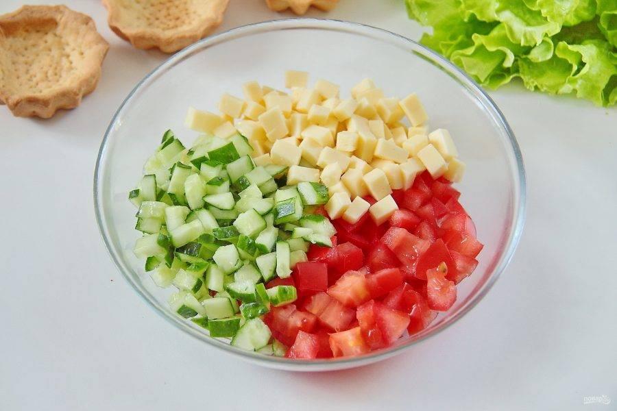 Для начинки нарежьте примерно одинаковыми кубиками сыр, помидор и огурец. Соедините все в глубокой миске или тарелке.