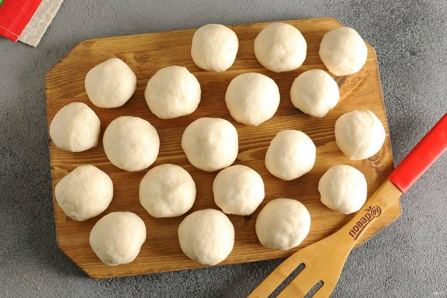 Разделите тесто на части, скатав из них шарики. В зависимости от желаемого размера пирожков, может получиться разное количество. У меня получилось 19 штук, каждый шарик весом примерно 50 грамм. Накройте шарики полотенцем, чтобы они не заветривались.