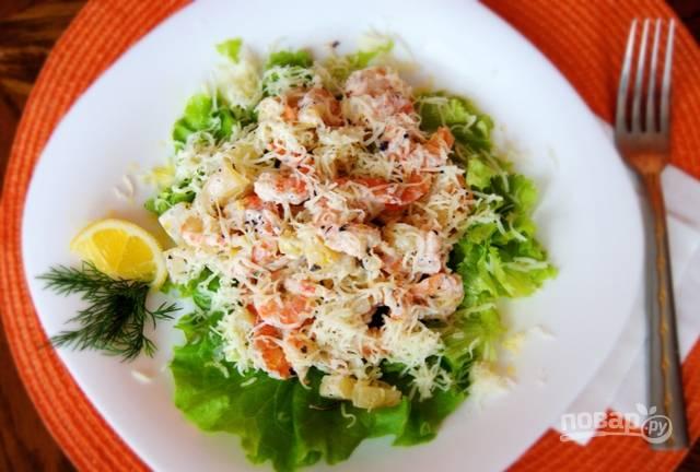 Креветки с ананасами выложите на промытые листья салата. Сверху налейте заправку, а также натрите на мелкой тёрке сыр. Приятного аппетита!