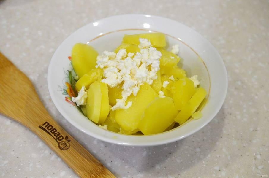 3. Добавьте к картофелю растопленное масло, чеснок и брынзу. Перемешайте.