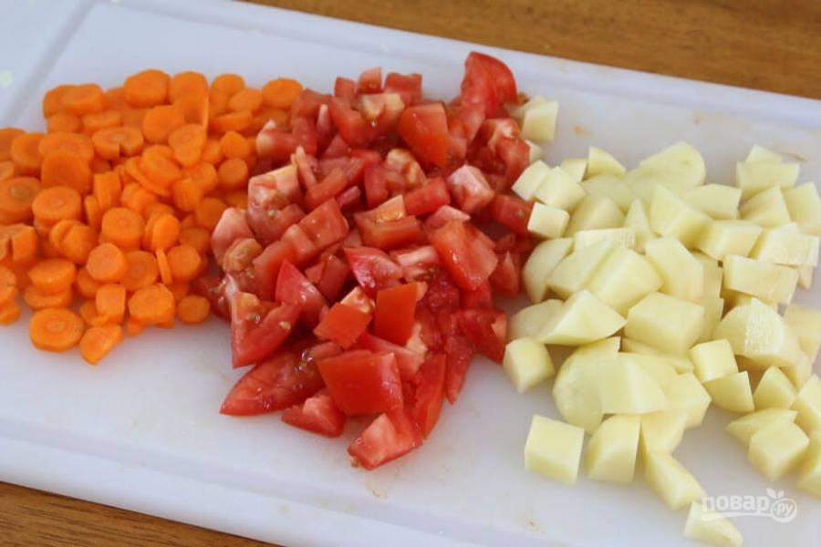 2.Очистите картофель, морковь. Морковь нарежьте кружочками, картофель и томаты -небольшими кубиками.