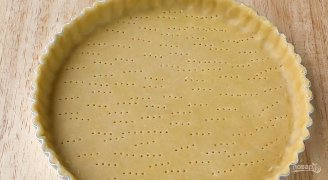 """1.Раскатайте ранее приготовленное песочное тесто в пласт размером с форму. Равномерно распределите тесто в форме, сформировав края. Наколите дно вилкой. Для теста нужны: 2-3 ст.л. холодной воды, яичный желток, 3/4 ч.л. соли, 90 г охлажденного сл. масла и 150 г муки. Муку соединим с солью и сливочным маслом, быстро разотрите руками до образования жирной крошки. После добавьте к крошке желток и воду. Быстро """"соберите"""" тесто, старайтесь особо не вымешивать его. Подержите его в холодильнике в пищевой пленке около получаса."""