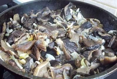 2. Обжарим грибы с луком примерно 20 минут, пока вся жидкость с грибов не испарится. Они должны потемнеть и чуть уменьшится в размерах. Специи - по вкусу, а вот масло использовать не рекомендую.