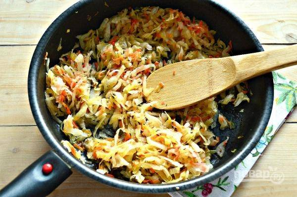 8. Квашеную капусту отожмите от рассола и выложите на сковороду с растительным маслом. Обжаривайте минут 7 на среднем огне, помешивая. После добавьте около стакана воды и оставьте тушиться, пока вся вода не уйдет.