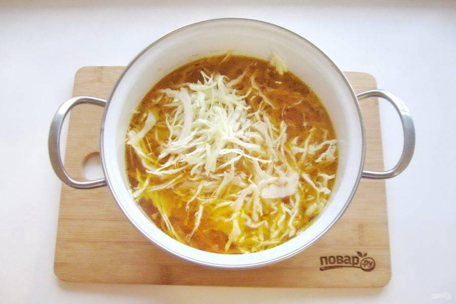 Через 10 минут выложите в кастрюлю картофель и нарезанную тонкой соломкой капусту.