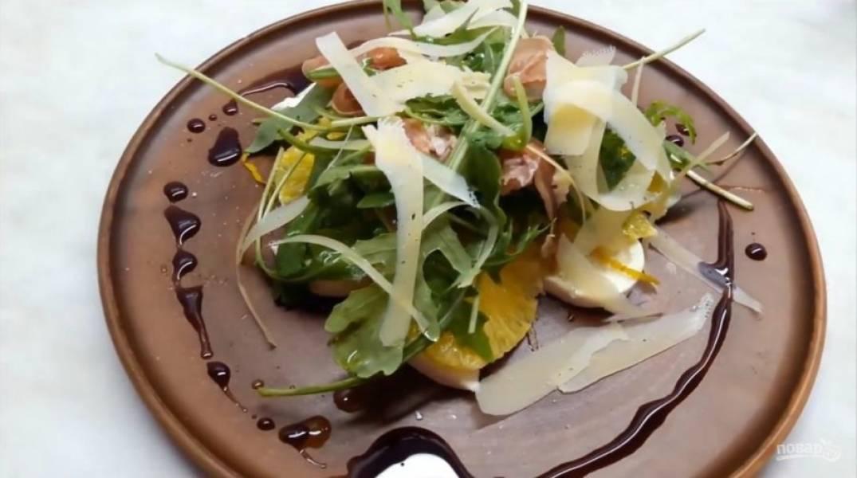 3. Выложите рукколу с ветчиной на основной салат. С помощью овощечистки нарежьте тонкими полосочками сыр. По краю тарелки налейте бальзамический уксус, чтобы он не окрасил сыр . Приятного аппетита!