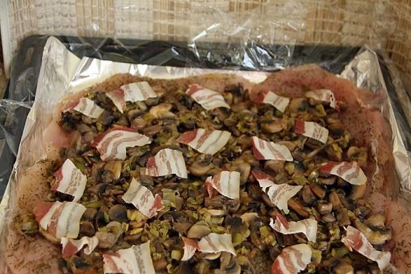 7. Выложить ровным слоем начинку из грибов. Чтобы придать блюду больше сочности, можно добавить пару мелко нарезанных ломтика бекона или сала.
