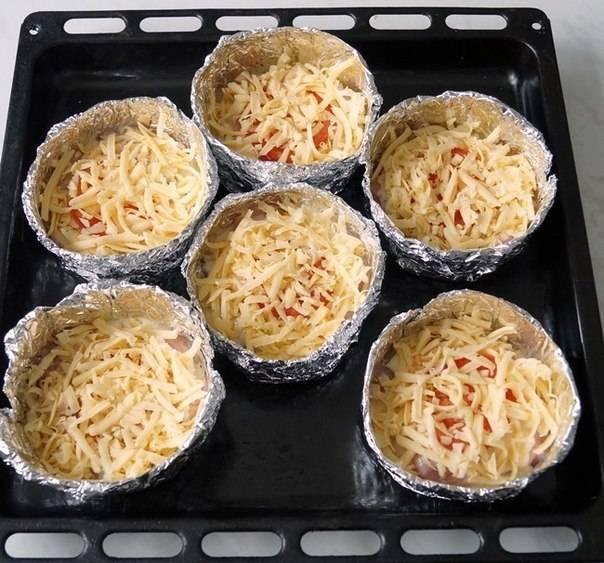 7. Сыр натереть на средней или мелкой терке и присыпать сверху. Формы поставить на противень и отправить в разогретую духовку на 20-25 минут, пока не появится аппетитная корочка, а курица хорошо проготовится.