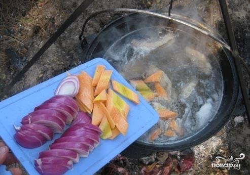 Красный лук порезать полукольцами, а морковь крупными кусками. Добавить в бульон.