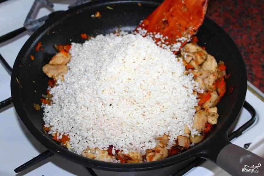 Вернуть овощи в сковороду с курицей, перемешать. Слить воду с риса и добавить его туда же. Разровнять лопаткой, воткнуть дольки чеснока, посолить и залить водой (она должна быть на 1 сантиметр выше уровня риса).