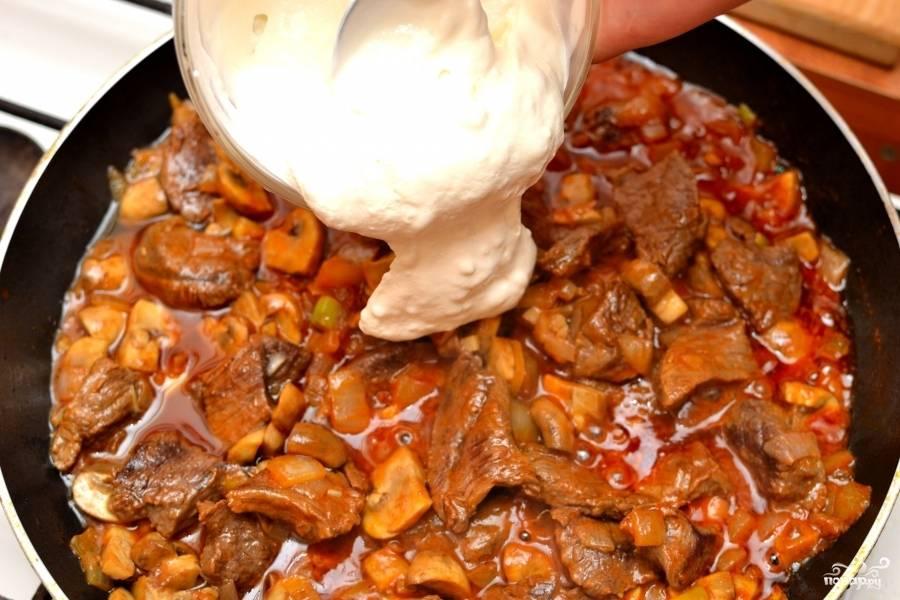 Когда все овощи будут готовы и говяжье филе тоже, выложите сметану. Помешайте. Потомите под крышкой ещё 7-10 минут. Ваша говядина тушёная с луком готова!