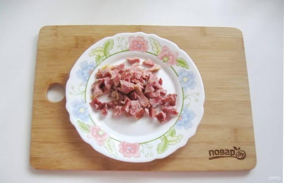 Достаньте ребрышки из кастрюли, снимите мясо с костей и мелко нарежьте.