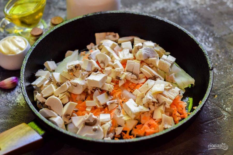 Вымойте и просушите шампиньоны, нарежьте небольшими кубиками и переложите к овощам в сковороду.