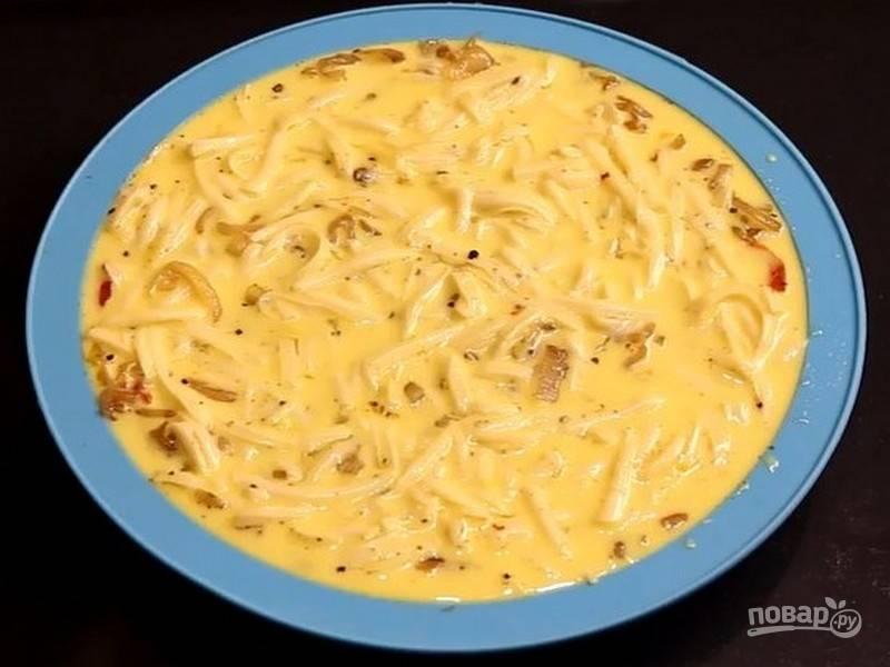 Полученной смесью залейте начинку, сверху посыпьте оставшимся тертым сыром и запекайте пирог 30 минут при 170 градусах.