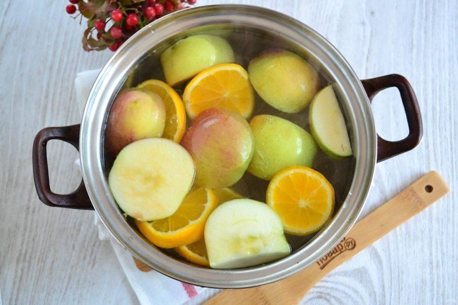 Вскипятите воду, отправьте в кастрюлю яблоки и апельсин, добавьте сахар. Проварите компот пару минут после закипания и снимите с огня.
