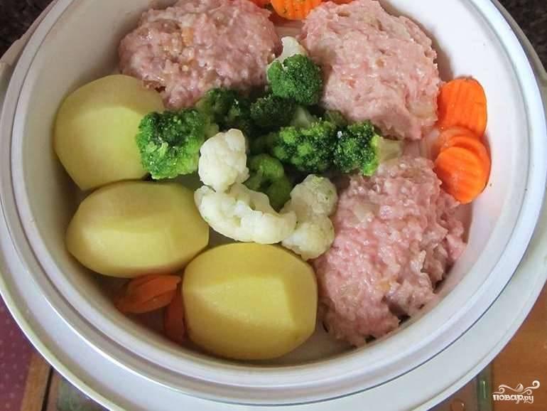 Все овощи помойте. Морковь и картофель почистите. Всё произвольно нарежьте. Уложите в ёмкость мультиварки котлетки.