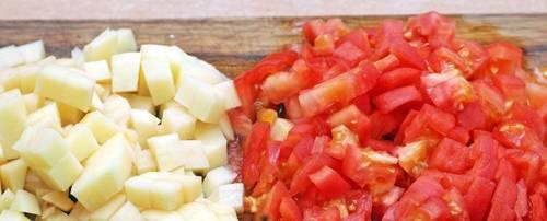 Капусту морковь и фасоль засыпаем в кипящую воду, варим 1 час. Тем временем, нарежьте две картофелины кубиками. С помидоров снимаем кожицу и также нарезаем кубиками. Через час добавляем все это в кастрюлю. Добавляем туда же половину стакана оливкового масла.