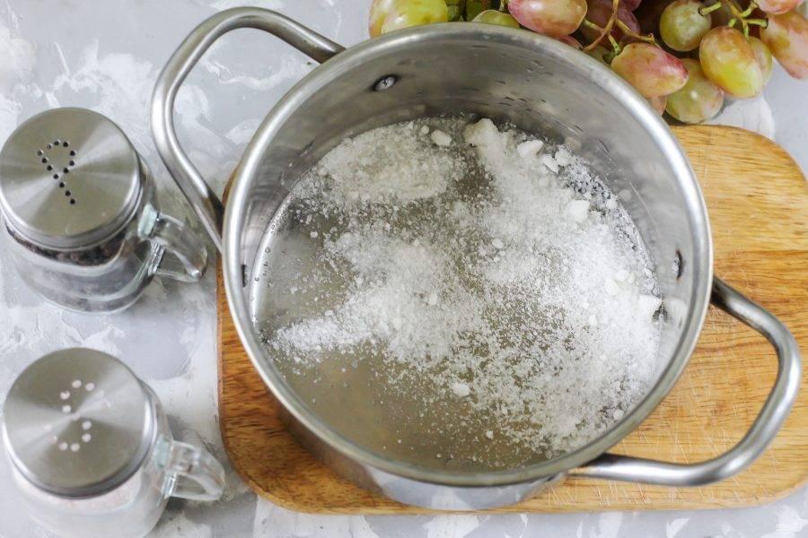 Всыпьте в кастрюлю соль. Если будете добавлять сахар, то всыпьте и его в кастрюлю. Слейте жидкость из банки с виноградом в кастрюлю, влейте еще 40-50 мл. воды и вскипятите рассол. Нагрев выключите и влейте уксус, перемешайте. Вливать уксус необходимо только в не кипящий рассол!