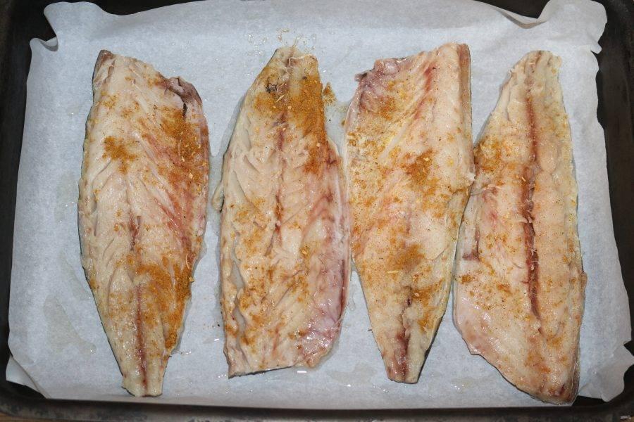 Форму для запекания застелите бумагой для запекания, слегка смажьте подсолнечным маслом. Выложите рыбу.