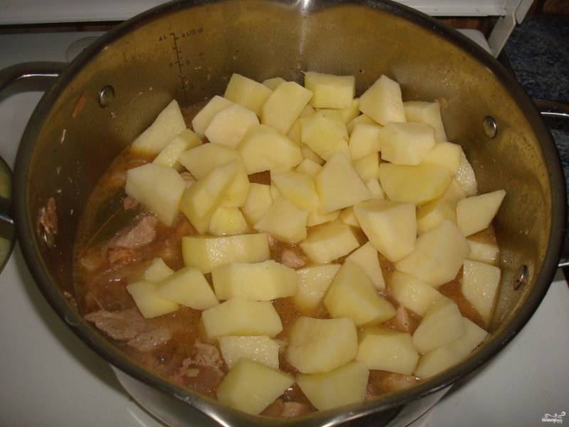За это время почистите и порежьте картошку кубиками. Добавьте ее затем к мясу.