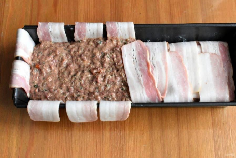 Форму смажьте маслом и выстелите тонкими ломтиками бекона. Выложите паштетный фарш и укройте его беконом.
