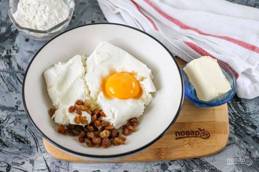 Творог любой жирности выложите в миску или глубокую тарелку, всыпьте туда же соль, вбейте куриное яйцо. Добавьте изюм. Предварительно его можно запарить в кипятке за час до приготовления сырников.