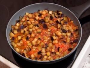 5. В середине жарки кладем баклажаны и помидоры. Обжариваем все до готовности на слабом огне.