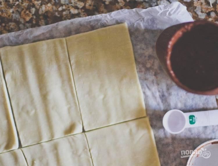 1.Разморозьте слоеное тесто, разрежьте его небольшими прямоугольниками.